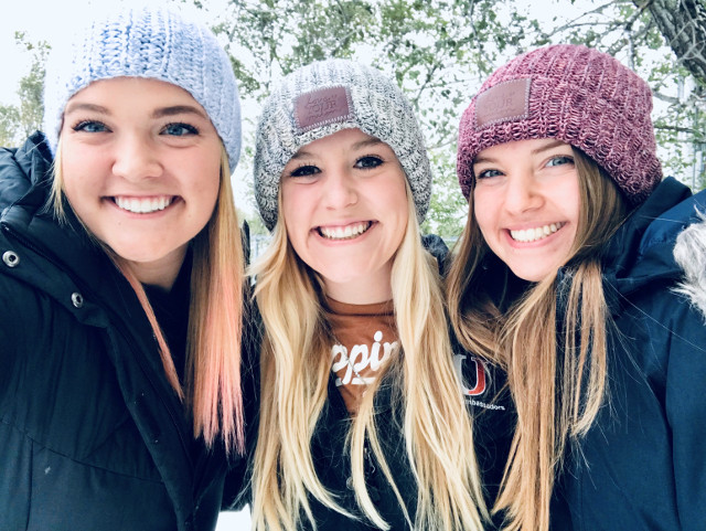 Ellie Michaletz posing with two friends in an outdoor winter setting.