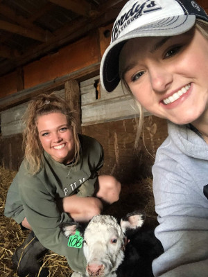 Ellie Michaletz with a friend and a calf in a barn.