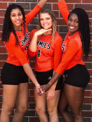 Ellie Michaletz posing with two volleyball friends in uniform.